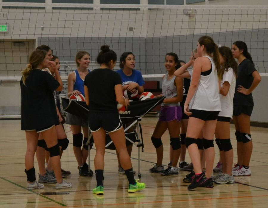 """The CAHS freshman girls' volleyball team huddle together one last time before their practice ends. After they huddled together they put their hands together and yelled ,""""Caimans!"""" in sequence. 'The team is tightly knit,"""" Kayla  D'Ambra (Middle Blocker) said. Together, everyone supports one another. Photo taken by Sierra Lagge."""