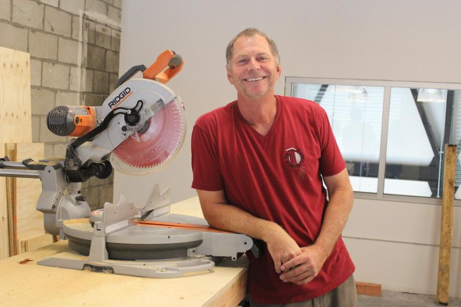Mr. Lundy poses by his saw in his private workshop located above the study hall. Courtesy of Ama Bonsu