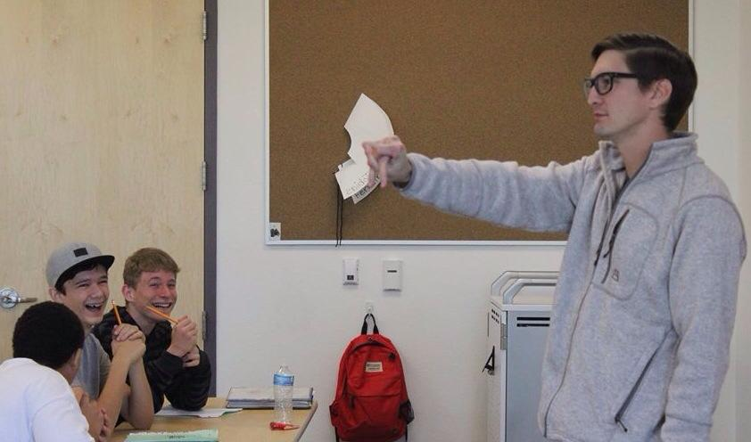 Mr. Ferreira shows his pre-algebra class a trick with his hands making his students burst out in laughter.