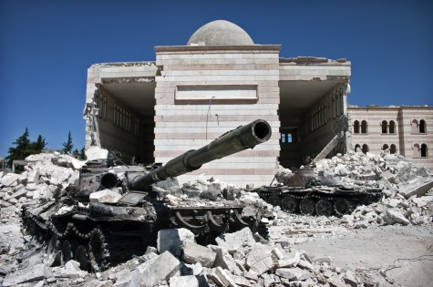 A destroyed Syrian tank sits among rubble in Azaz, Syria. Photo from Wikimedia Commons.