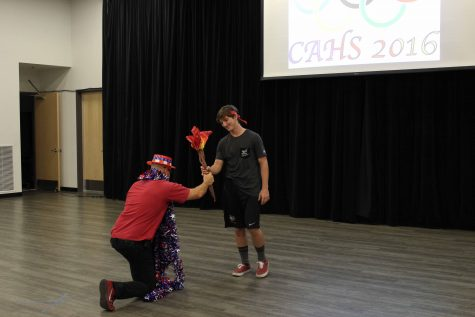 Principal Dana Moen presents the CAHS Olympic Torch to ASB President and senior Jacob Mizel.