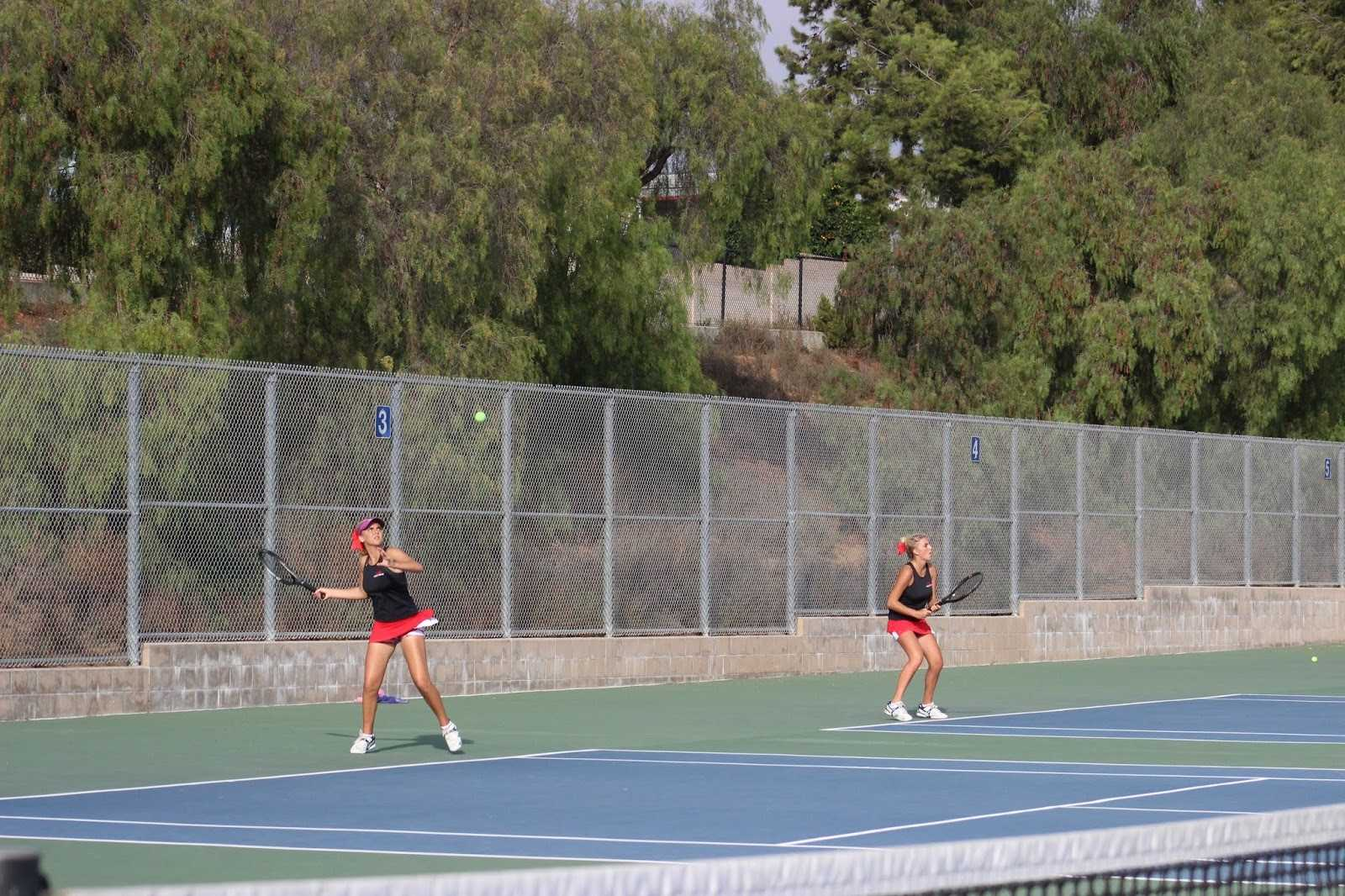 <em><strong>A Sibling Match.</strong></em> Sisters Lexie and Taylee Mann-Shomo play intense matches on courts next to one another. Photo taken by Lauryn Butler.