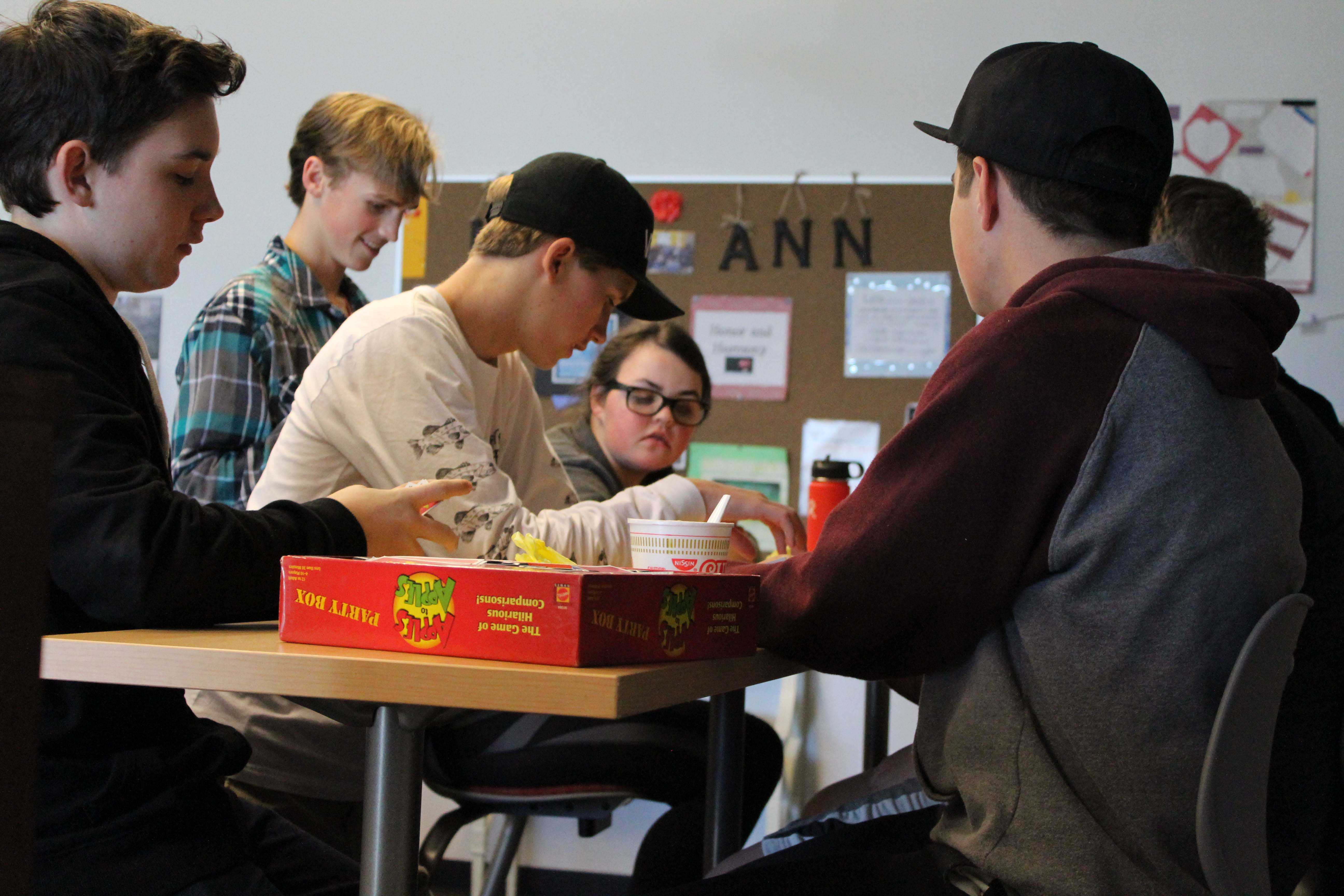 Club members engage in a game of 'Apples To Apples.'
