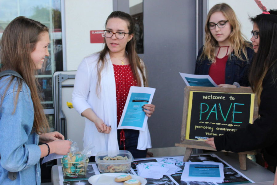 Senior Anastasia Reimann educates a fellow student about PAVE at their lunchtime Valentine's Day Event. Photo credit Brigid Ambuul.